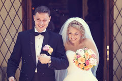 Noivo e noiva que saem da igreja Imagens de Stock