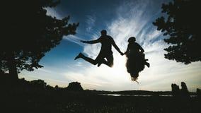 Noivo e noiva que saltam contra o céu bonito fotografia de stock royalty free
