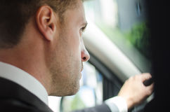 Noivo elegante no traje que conduz o carro à moda na luz solar Imagens de Stock Royalty Free