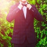 Noivo em um terno azul, camisa branca do close up que corrige um laço em um fundo de um arbusto verde O homem em um terno Imagem de Stock