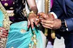 Noivo indiano que põe o anel sobre a noiva indiana imagem de stock royalty free