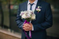 Noivo no ramalhete do casamento da tomada do casaco azul imagem de stock