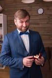 Noivo no terno luxuoso que guarda a caixa com aliança de casamento foto de stock royalty free
