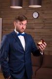 Noivo no terno luxuoso que guarda a caixa com aliança de casamento fotografia de stock royalty free