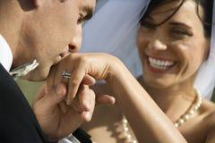 Noivo que beija a mão da noiva imagens de stock royalty free