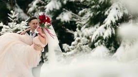 Noivo que gerencie a noiva feliz que guarda e que gerencie a em suas mãos na floresta do abeto vermelho da árvore de abeto do tem filme