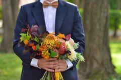 Noivo que guarda flores de um ramalhete do casamento Imagem de Stock Royalty Free