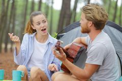 Noivo que joga o sócio da guitarra que canta fora da barraca fotografia de stock