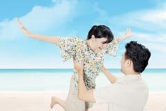 Os pares felizes atrativos têm o divertimento na praia Imagem de Stock