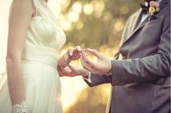 Noivo que põe a aliança de casamento sobre o dedo da noiva Fotografia de Stock Royalty Free