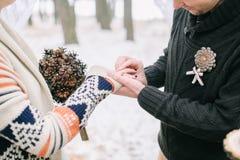 Noivo que põe a aliança de casamento sobre o dedo das noivas Foto de Stock Royalty Free