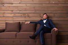 Noivo sério no terno e laço que senta-se no sofá imagem de stock royalty free