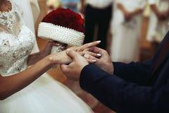 Noivo seguro à moda que põe a aliança de casamento sobre a noiva bonita fotografia de stock