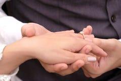 Noivo tailandês do casamento que põe uma aliança de casamento sobre o dedo do ` s da noiva imagens de stock royalty free