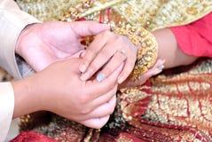 Noivo tailandês do casamento que põe uma aliança de casamento sobre o dedo do ` s da noiva imagens de stock