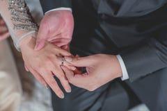 Noivo tailandês que põe uma aliança de casamento Fotos de Stock Royalty Free