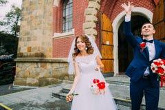 Noivos alegres que saem da igreja após uma cerimônia de casamento Fotografia de Stock Royalty Free