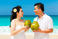 Noivos asiáticos em uma praia tropical Casamento e lua de mel Fotografia de Stock
