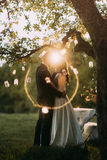 Noivos bonitos que beijam no por do sol sob a árvore decorada com muitas lanternas Fotos de Stock Royalty Free
