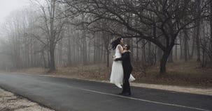 Noivos, dança e jogo com emoção na estrada perto da floresta, lenta 4K video estoque
