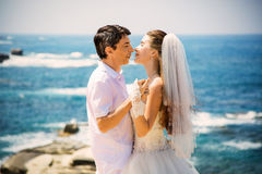 Noivos de sorriso elegantes que andam na praia, beijando, cerimônia de casamento, mar Mediterrâneo Foto de Stock