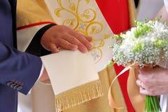 Noivos durante a troca das alianças de casamento na igreja Imagens de Stock Royalty Free