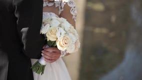 Noivos elegantes que levantam junto fora em um dia do casamento Noiva que guarda um ramalhete branco da rosa ao estar video estoque