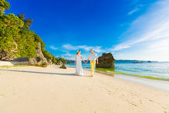 Noivos em uma praia tropical com o por do sol no backg Fotografia de Stock