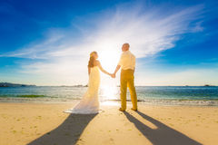 Noivos em uma praia tropical com o por do sol no backg Fotografia de Stock Royalty Free