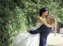 Noivos engraçados que abraçam na rua Imagem de Stock Royalty Free