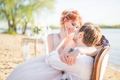 Noivos felizes dos pares que sentam-se em uma cadeira na costa de um lago Imagens de Stock Royalty Free