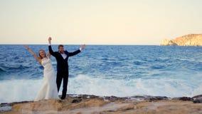 Noivos felizes no litoral em seu dia do casamento Conceito feliz da lua de mel filme