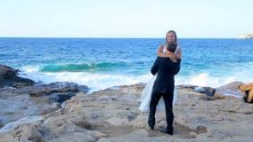 Noivos felizes no litoral em seu dia do casamento O conceito de uma vida familiar feliz vídeos de arquivo