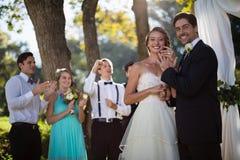 Noivos felizes que mostram o anel de noivado no parque foto de stock