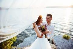 Noivos louros bonitos bonitos elegantes nas rochas, ami Foto de Stock Royalty Free