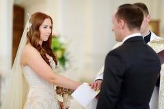 Noivos na igreja durante um casamento Fotografia de Stock