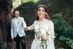 Noivos no dia do casamento, abra?ando, estando perto de uma rocha ou de uma grande pedra fotos de stock royalty free