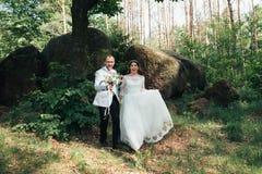 Noivos no dia do casamento, abra?ando, estando perto de uma rocha ou de uma grande pedra foto de stock royalty free