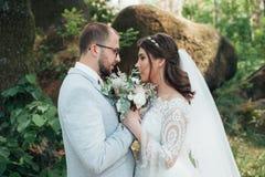 Noivos no dia do casamento, abra?ando, estando perto de uma rocha ou de uma grande pedra fotografia de stock royalty free