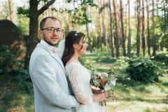 Noivos no dia do casamento, abra?ando, estando perto de uma rocha ou de uma grande pedra imagens de stock royalty free