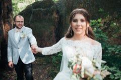 Noivos no dia do casamento, abra?ando, estando perto de uma rocha ou de uma grande pedra foto de stock