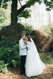 Noivos no dia do casamento, abra?ando, estando perto de uma rocha ou de uma grande pedra fotografia de stock