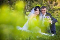 Noivos que abraçam e que olham nos olhos outro de um assento em uma grama verde Fotos de Stock Royalty Free