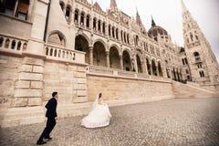 Noivos que abra?am na rua velha da cidade O par do casamento anda em Budapest perto da casa do parlamento foto de stock royalty free