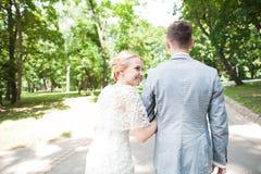 Noivos que andam afastado no parque do verão fora Fotografia de Stock Royalty Free