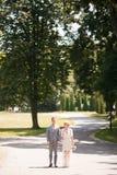 Noivos que andam afastado no parque do verão fora Imagens de Stock