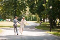 Noivos que andam afastado no parque do verão fora Fotos de Stock