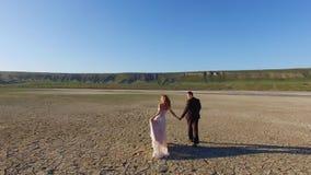 Noivos que andam na terra da textura Lago de sal seco filme