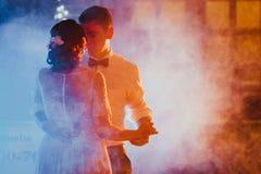 Noivos que dançam a primeira dança no fundo obscuro foto de stock royalty free