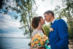 Noivos que estão de beijo no fundo da natureza imagens de stock royalty free
